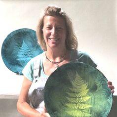 Smiling photo of Noelle Trese holding a large bowl decorated with the silhouette of a leaf